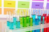Provrör med färg vätska på färg prover bakgrund — Stockfoto