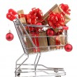 Beautiful golden gifts with red ribbon and Christmas balls in  shopping cart isolated on white — Stock Photo