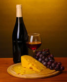 Bottle of great wine with wineglass and cheese on wooden table on brown background — Stock Photo