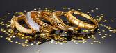 Beautiful golden bracelets on grey background — Стоковое фото