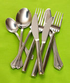 Forks, spoons and knives on a green tablecloth — Stock Photo