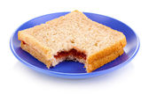 Bitten sandwich with jam on plate isolated on white — Stock Photo