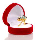 Gold ring with blue, black, lilac and clear crystals in red velvet box isolated on white — Stock Photo