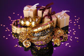 Beautiful golden jewelry and gifts on purple background — Stock Photo