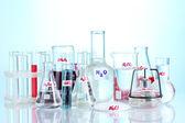 Tubos de ensaio com vários ácidos e produtos químicos em fundo azul — Foto Stock