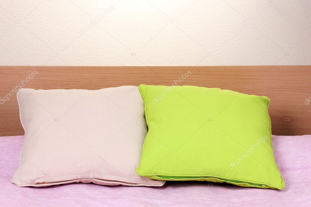 Bright pillows on bed on beige background — Stock Photo #10654191