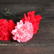 Stock Photo: Bouquet of carnations on wooden background