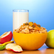 Tasty cornflakes in yellow bowl, apples and glass of milk on wooden table on blue background — Stock Photo #10730562