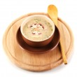 Tasty soup on wooden round board isolated on white — Stock Photo