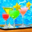 Glasses of cocktails on wooden table on blue sea background — Stock Photo