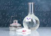 Zkumavky s různými kyselinami a dalších chemikálií na pozadí tabule — Stock fotografie