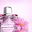 Women's perfume in beautiful bottle and flower on pink background — Stock Photo #8113246
