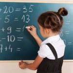 Beautiful little girl writing on classroom board — Stock Photo #8113389