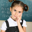 Stock Photo: Beautiful little girl standing near blackboard in the classroom