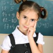 Beautiful little girl standing near blackboard in the classroom — Stock Photo