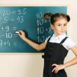 Beautiful little girl writing on classroom board — Stock Photo