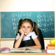 Little schoolchild in classroom near blackboard - Stock Photo