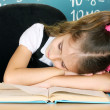 Little schoolgirl sleep in classroom near blackboard — Stock Photo