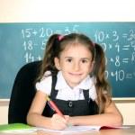 Little schoolchild in classroom near blackboard — Stock Photo #8113448