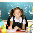Little schoolchild in classroom near blackboard — Stock fotografie