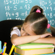 Little schoolgirl sleep in classroom near blackboard - Stock Photo