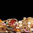 Various gold jewellery on black background — Stock Photo #8113525