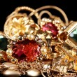 Various gold jewellery on black background - Stock Photo