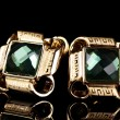 Beautiful gold earrings with emerald on black background - Photo