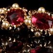 Beautiful gold earrings with rubies and pearls on black background - Stock Photo
