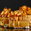 Various gold jewellery and gifts on black background — Stock Photo #8113561