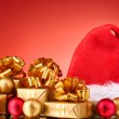 Beautiful Christmas hat, gifts and Christmas balls on red background — Stock Photo