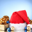 Beautiful Christmas hat, gifts and Christmas balls on blue background — Stock Photo