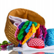 Bright threads for needlework and fabric in a wicker basket — Stock Photo #8114230