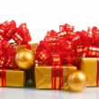 Royalty-Free Stock Photo: Beautiful golden gifts with red ribbon and Christmas balls isolated on whit