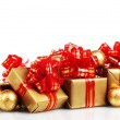 Stock Photo: Beautiful golden gifts with red ribbon and Christmas balls isolated on whit