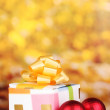 Christmas balls and gift on yellow background — Stock Photo #8114850