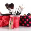 Red glass with brushes and makeup bag with cosmetics isolated on white — Stock Photo #8114914
