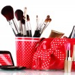 red glass with brushes and makeup bag with cosmetics isolated on white — Stock Photo