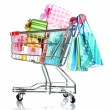 Shopping cart with bright gifts and paper bags isolated on white — Stock Photo #8115131