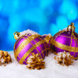 Beautiful purple Christmas balls and cones in snow on blue background — Stock Photo