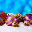 Beautiful purple Christmas balls and branch on snow on blue background — Stockfoto #8115381