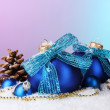 Beautiful blue Christmas balls and cones on snow on bright background — Stock Photo