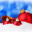 Beautiful red Christmas balls in snow on blue background — Stock Photo
