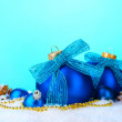 Beautiful blue Christmas balls and cones on snow on blue background — Stock Photo