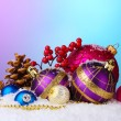 Beautiful Christmas balls and cones on snow on bright background — Stock Photo