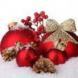 Beautiful red Christmas balls and cones on snow isolated on white — Stock Photo