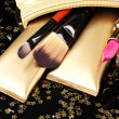 Beautiful golden makeup bag and cosmetics isolated on black — Stock Photo