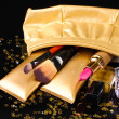 Beautiful golden makeup bag and cosmetics isolated on black — Stock Photo #8115705
