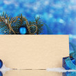 Blank postcard, Christmas balls and fir-tree on blue background - Lizenzfreies Foto