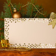 Blank postcard, Christmas balls and fir-tree on wooden table on brown backg - Stock Photo